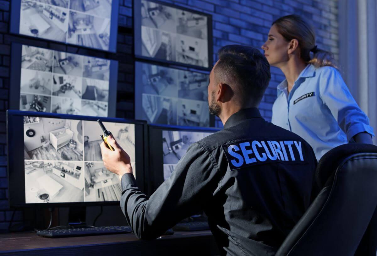 Sicherheitsleute prüfen Bildschirme mit Videoüberwachung