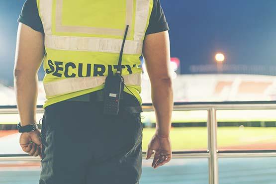 Sicherheitsdienst mit Weste und Funkgerät im Stadion